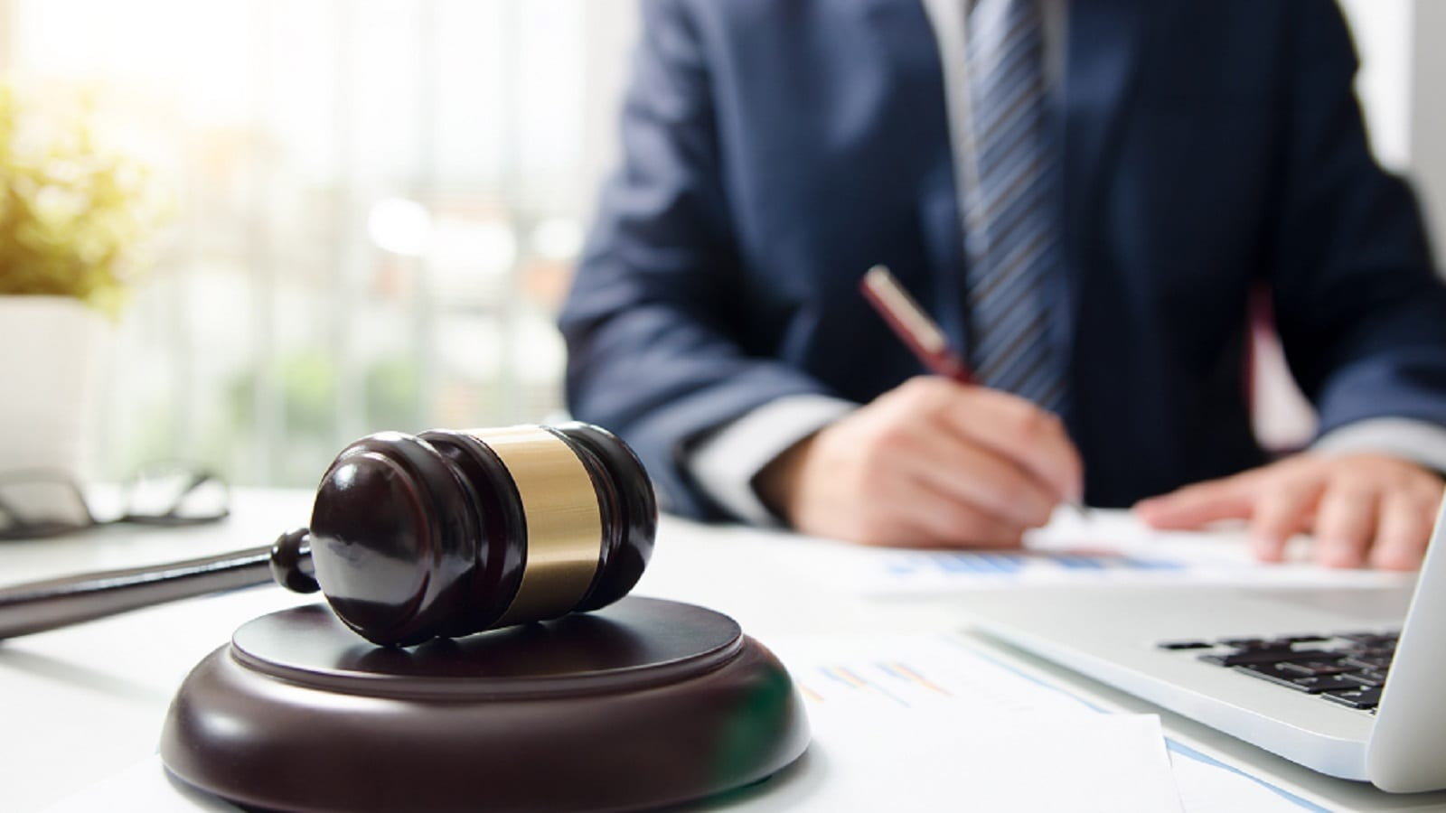 Attorney Signing A Document Next To A Wooden Gavel