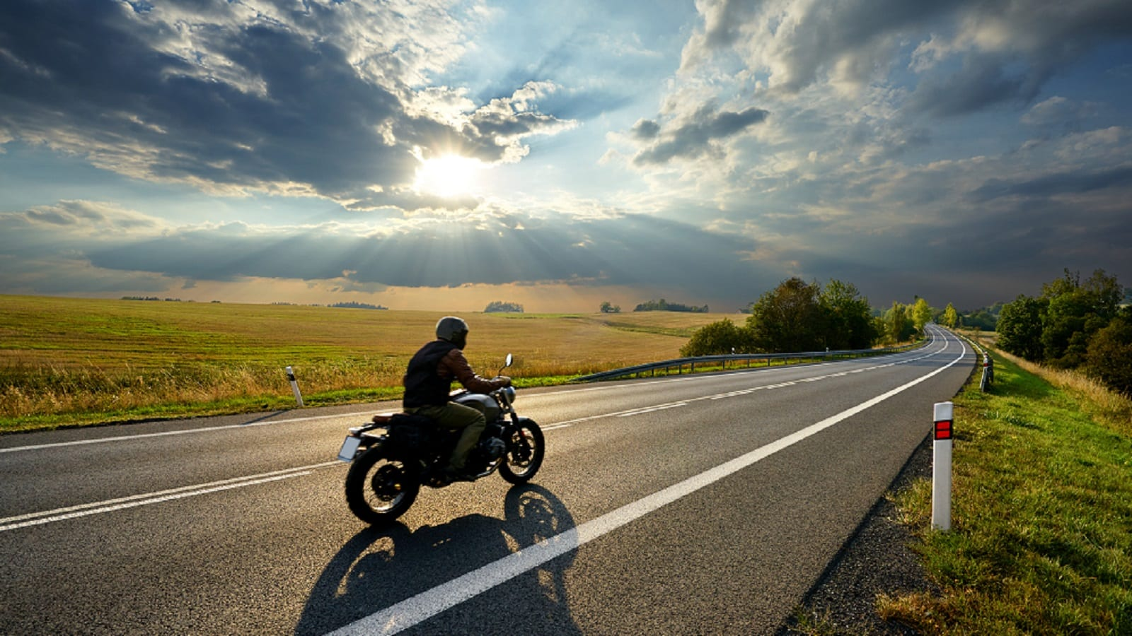 Man Riding Motorcycle In Rural Area Stock Photo