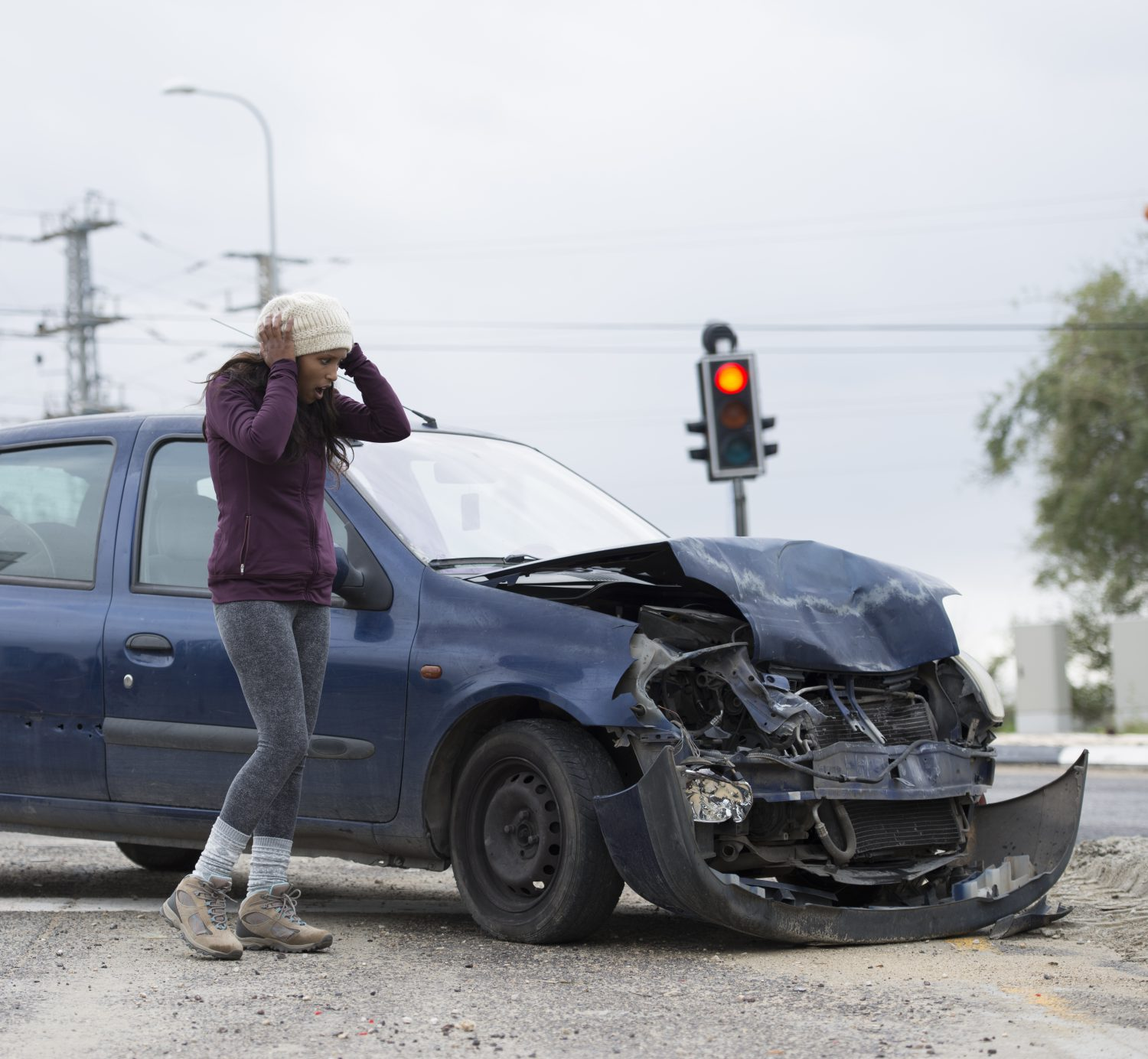 Woman with shocked face looking on her damaged car, holding head in hands. Car accident with frontal impact. Red traffic light is on background.
