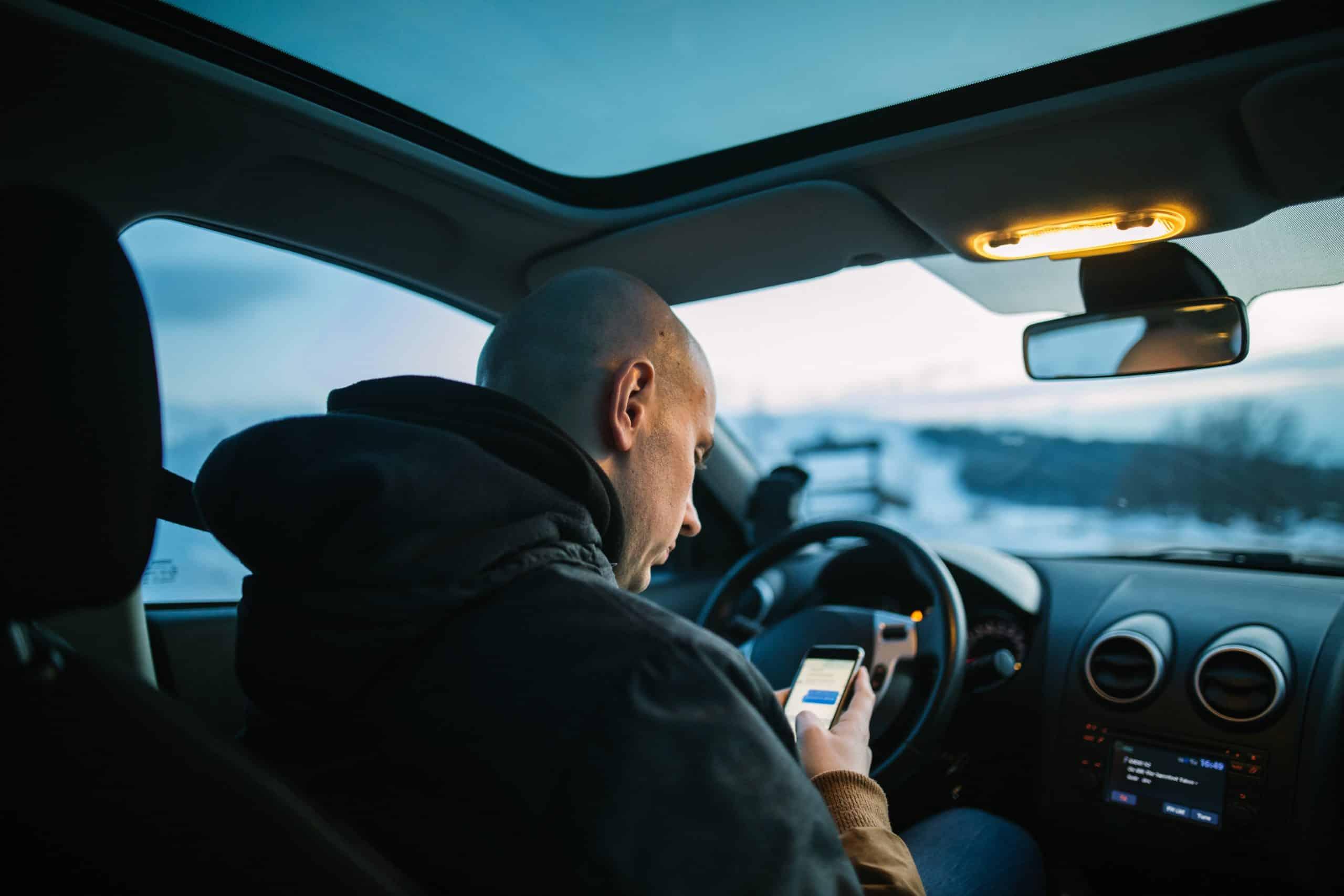 man sitting in car using his smart phone