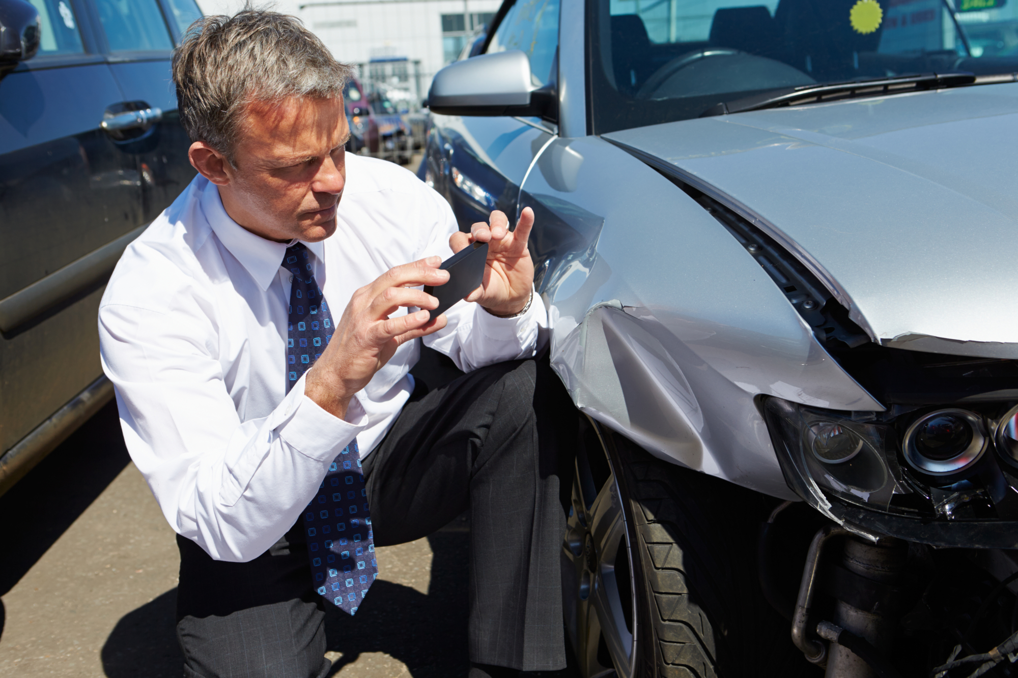 insurance adjuster documenting damage after a car accident