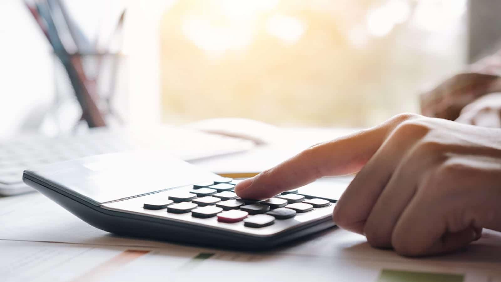 Hand On Calculator Stock Photo