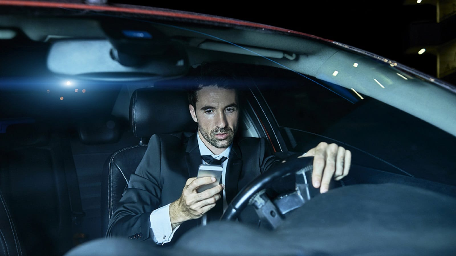 Man In Business Suit Texting While Driving